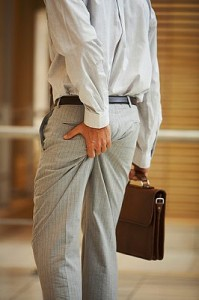 Businessman squeezing his behind